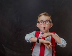 School kid in school uniform and smart watch. Pupil in glassesand with bag looking at the watch to know time. Boy worried and afraid about deadline and to be late