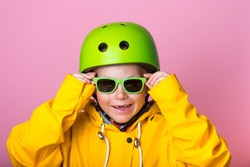 School kid is in green protect helmet and sunglasses and yellow coat isolated on pink. Funny face of blond freckled child boy pointing with thumb up. Extreme sport for children. Safety. Life insurance