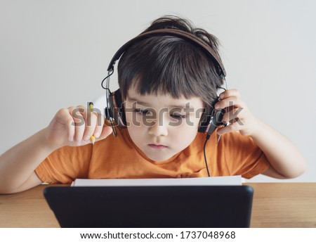 School kid wearing headphone listening the teacher teaching online class,Child boy studying and doing homework on digital pad,Home schooling,Distance education, e-learning online with new normal life