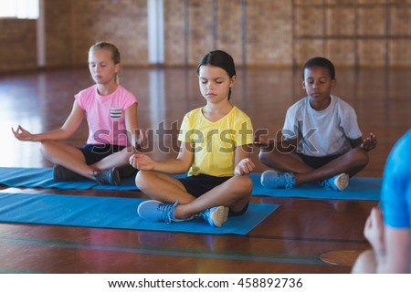 School kids meditating during yoga class in basketball court at school gym