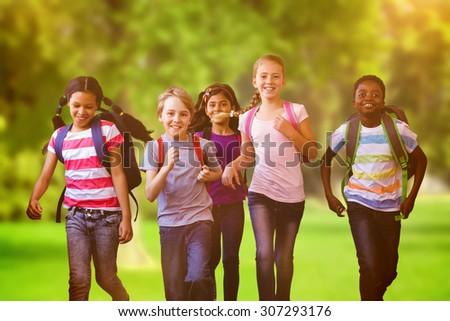 School kids running in school corridor against trees and meadow