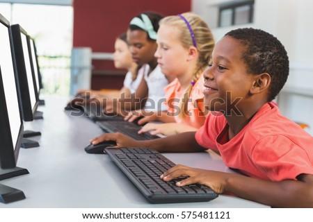 school kids using computer in...