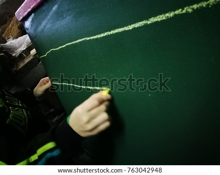 School life. A pupil is lining on a chalkboard. Yellow chalk is in use. Writing lession. Lines. #763042948