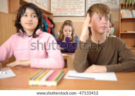 School life routine. Bored girl on second desk is in primary focus. Shallow depth of field.