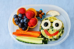 school lunch box for kids with food in the form of funny faces. the toning. selective focus