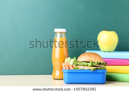 School lunch box with sandwich and bottle of juice on chalkboard background