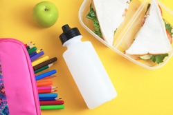 School lunch. Sandwich and green apple, bottle of water, healthy eating concept, colorful pencils over  yellow background.