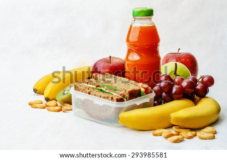 school lunch with a sandwich, fresh fruits, crackers and juice. the toning. selective focus