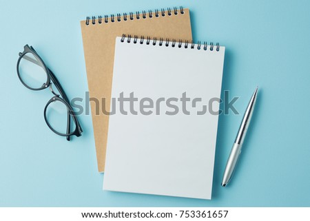 school notebook on a blue background, spiral notepad on a table #753361657