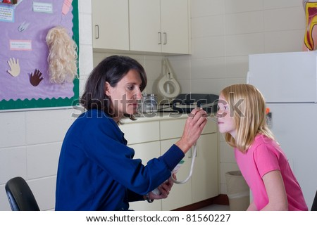 School nurse checking temperature of student patient.