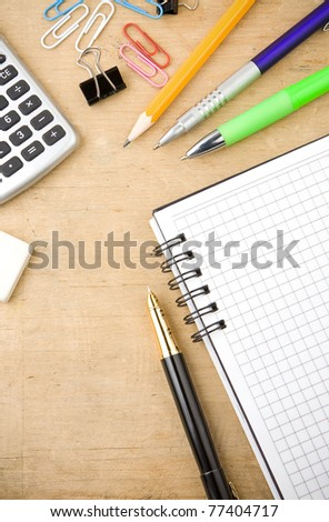school, office accessories and checked notebook on wood texture