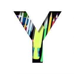 School or office supplies font. The letter Y cut out of paper on a background of a set of stationery for school, study or office with black backdrop. Decorative alphabet, font collection.
