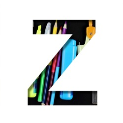 School or office supplies font. The letter Z cut out of paper on a background of a set of stationery for school, study or office with black backdrop. Decorative alphabet, font collection.