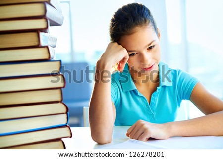 School pupil being frustrated with the amount of books to read