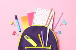 School stationery and school backpack on a colored background top view. concept: back to school