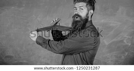 School stationery. Man scruffy use stapler dangerous way. Hipster teacher formal wear necktie holds stapler. Teacher bearded man with pink stapler chalkboard background. School accident prevention.