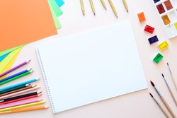 School stationery on pink paper. Colored pencils, pens, pains, paper, brushes for school and student education. Back to school. Copy space. Top view. Flat lay