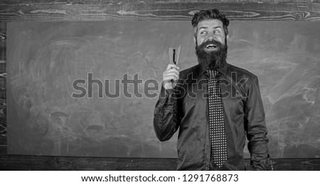 School stationery. Prepare for school season buy stationery. Man smiling hold stapler stationery. Hipster teacher formal necktie holds stapler. Teacher bearded man with stapler chalkboard background.