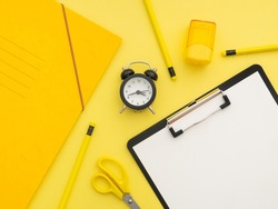 School stationery supplies, back to school concept. Paper clipboard, yellow scissors, black alarm clock, notebook, pencils and yellow sharpener isolated on yellow background