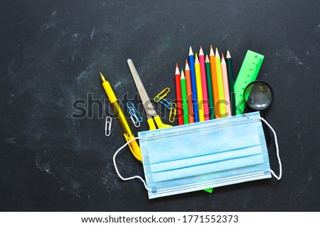 School stationery supplies, medical masks on the blackboard. back to school after covid-19 coronavirus.Concept of learning, maintaining social distance