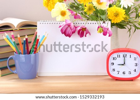 school still life. textbooks, an alarm clock, colored pencils, a bouquet of flowers and a blank paper album . study, education. blank space for your text.