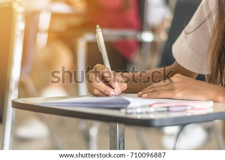 School student's taking exam writing answer in classroom for education and literacy concept