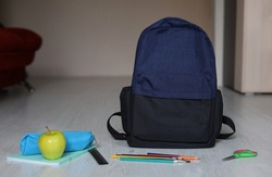 School supplies and a briefcase are on the floor at home. The concept of back to school. Selective focus