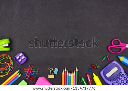 School supplies bottom border on a chalkboard background with copy space