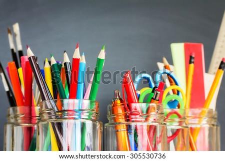 School supplies in jars against the blackboard