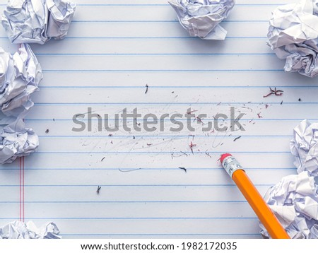 School supplies of blank lined notebook paper with eraser marks and erased pencil writing, surrounded by balled up paper and a pencil eraser. Studying or writing mistakes concept. ストックフォト ©