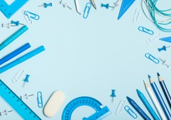 School supplies of blue and white colors on a blue background. Male or boyish still life on the topic of school, study, office work. Flat lay