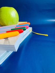 School supplies on blue background. Soon to school. Items for lessons and classes. Books are stacked, colorful markers and a green apple are on them. Healthy snack. Home schooling and homework.