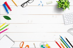 School supplies on white wooden desk. Top view, flat lay composition with copy space in the middle