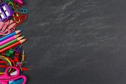 School supplies side border on a chalkboard background