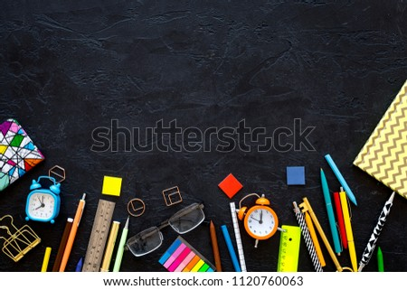 School supplies. Student stationery mockup with glasses and notebook  on black background top view copy space #1120760063