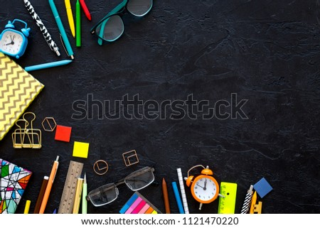 School supplies. Student stationery mockup with glasses and notebook  on black background top view copy space #1121470220