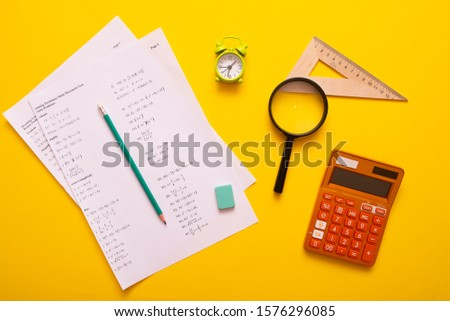 School supplies used in maths. Maths drawing tools. Maths equation exercise sheet with school drawing tools. Close-up of simple maths equation.