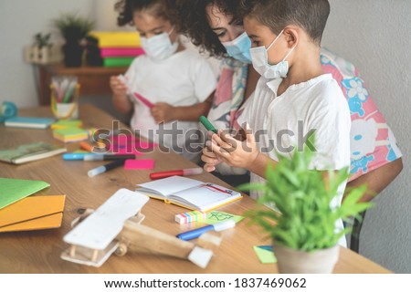 School teacher helping children in classroom while wearing safety masks - Focus on boy's face ストックフォト ©