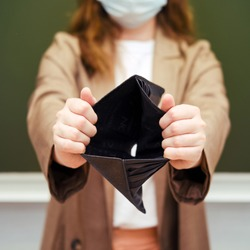 School teacher in a medical mask with a hole in the wallet with no money
