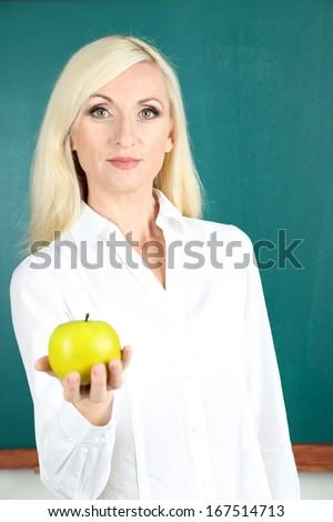 School teacher near blackboard with apple in classroom