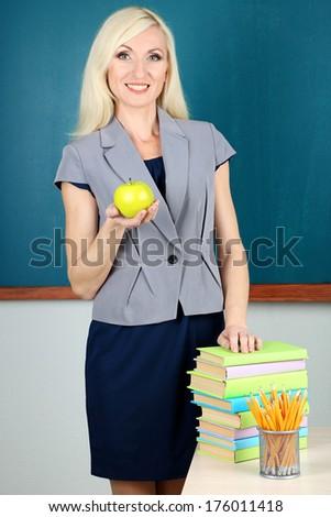 School teacher with apple on blackboard background
