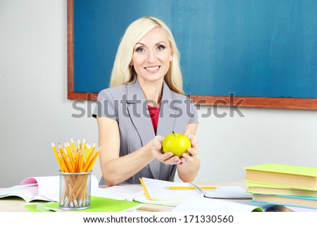 School teacher with apple sitting at table on blackboard background