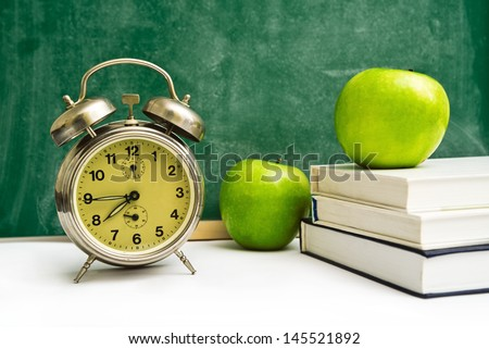School time again. Clock, apples and books on teacher\'s table, green chalkboard in background. Back to school.