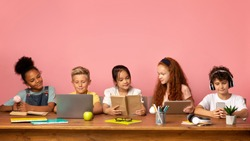 School time. Multiethnic kids with different gadgets and books sitting at table against pink background, empty space. Panorama