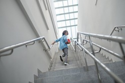 School time. Smiling schoolboy walking upstairs with pile of books