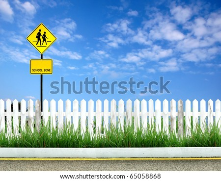 School warning sign with white fence and blue sky