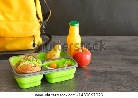 Schoolbag and lunch box with tasty food on table