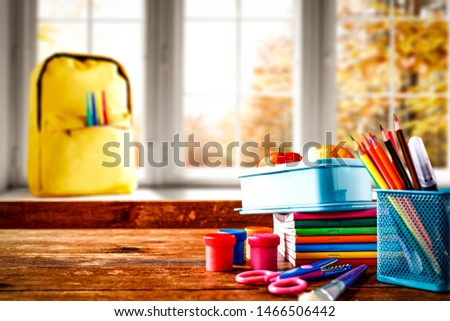 Schoolbags background with some school supplies on wooden desk top and a windowsill with white window autumn view. Empty space for product and decoration.