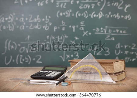 Schoolbooks and calculator lying on a wooden school desk in front of a green chalkboard with Mathematical formulas school