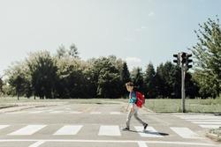 Schoolboy crossing road on way to school